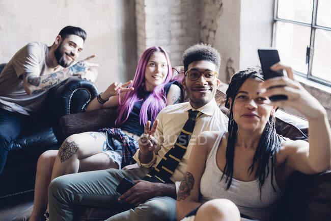 Grupo de amigos sentados en un sofá en un altillo tomando una selfie - foto de stock