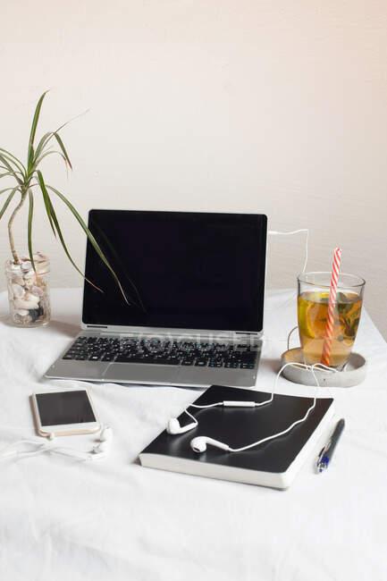 Teléfono móvil con libro y té por ordenador portátil en el escritorio contra la pared en la oficina - foto de stock