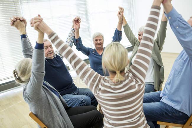 Grupo de personas mayores que practican gimnasia de silla con instructor en casa de retiro - foto de stock