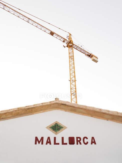 Промисловий журавель нависає над ясним небом позаду будинку в Мальорці. — стокове фото