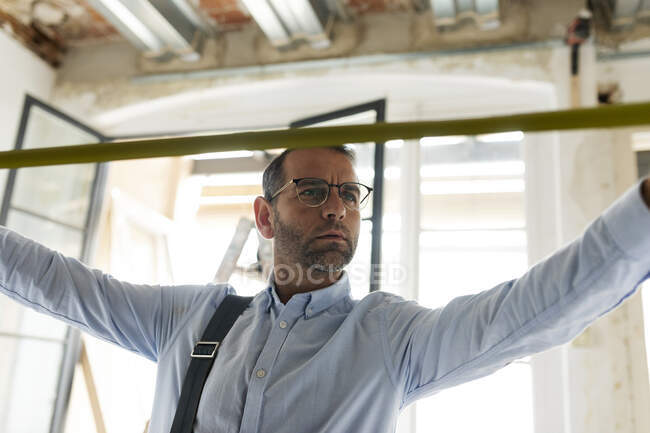 Architecte utilisant un ruban à mesurer dans une maison en construction — Photo de stock