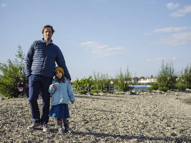 Padre con hija de pie en tierra contra el cielo durante el día soleado - foto de stock