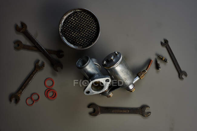 Top view of vintage carburetor with tools in front of grey background — Stock Photo