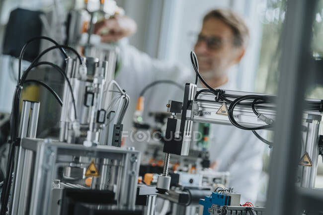 Close-up of machinery with male scientist in background at factory — Stockfoto