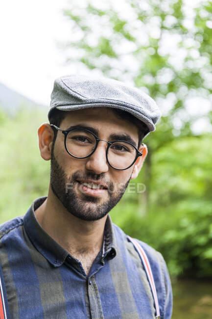 Ritratto di giovane uomo con occhiali e cappello — Foto stock
