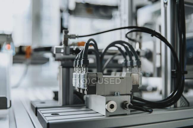 Крупный план оборудования с кабелями на столе в лаборатории на заводе — стоковое фото