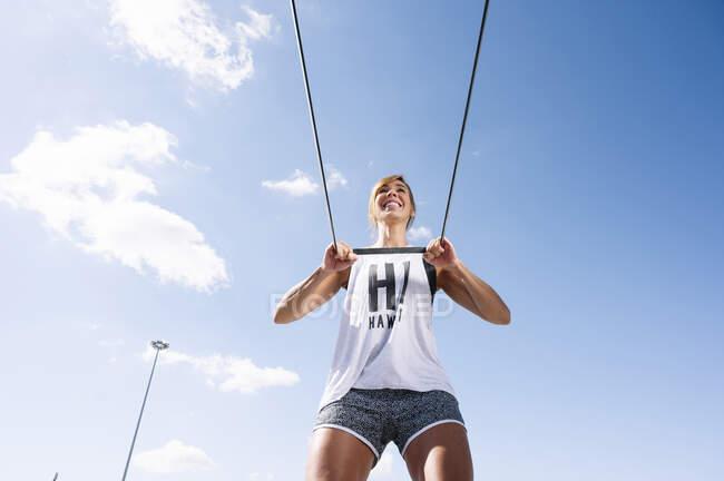 Sorrindo mulher adulta média exercitando com alça contra o céu durante o dia ensolarado — Fotografia de Stock