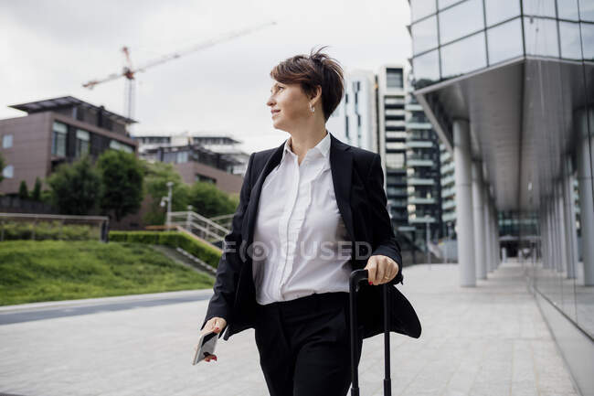 Female professional with suitcase walking on footpath in city — Fotografia de Stock