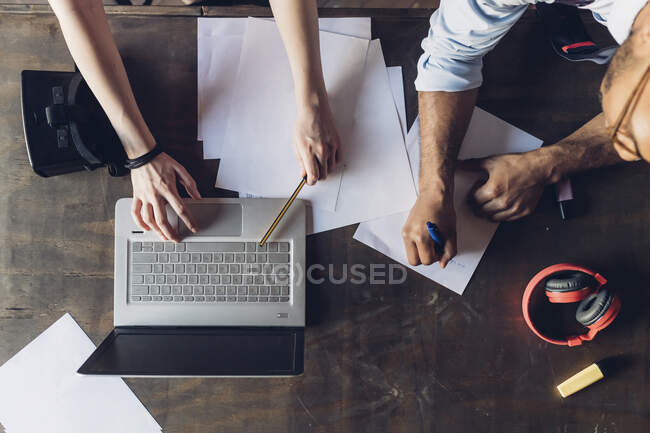 Two creative business people working with laptop and papers on wooden table — Stock Photo