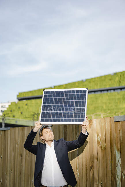 Businessman with closed eyes standing at a boarding holding up solar panel — Stock Photo