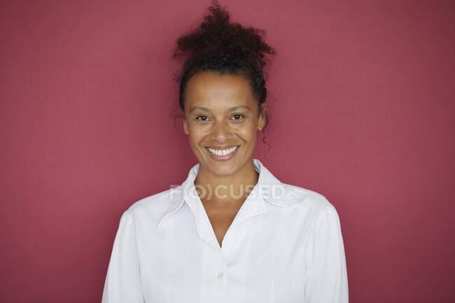 Retrato de empresaria sonriente sobre fondo rojo - foto de stock