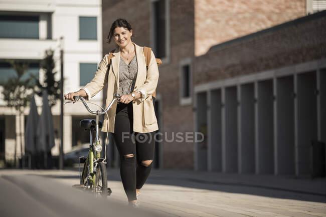 Caminata sonriente con bicicleta en la calle de la ciudad - foto de stock