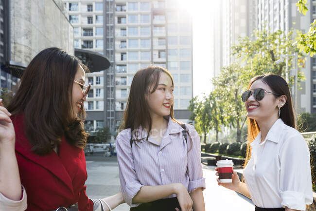 Female friends talking while standing against buildings in city - foto de stock