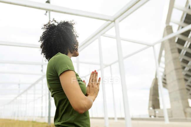 Посеред дорослої жінки, яка медитує, стоячи проти збудованої споруди в місті. — стокове фото
