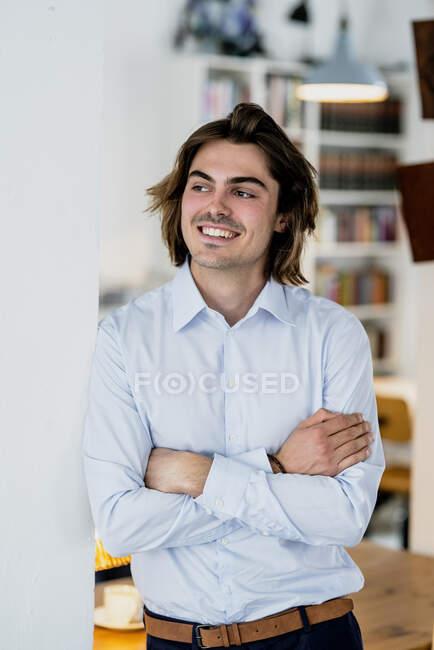 Lächelnder männlicher Profi mit verschränkten Armen im Café an der Wand stehend — Stockfoto