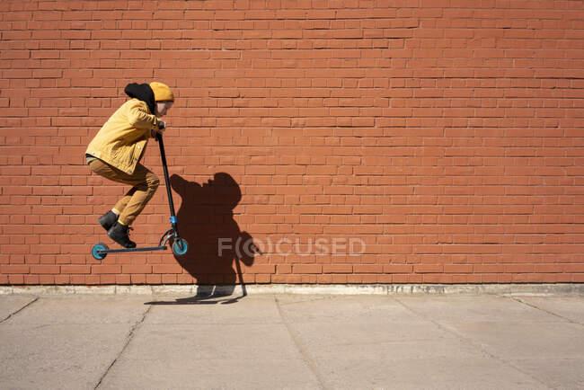 Chico realizando truco con vespa de empuje en la acera contra la pared de ladrillo durante el día soleado - foto de stock