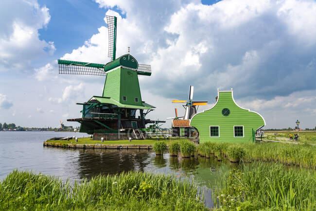 Países Bajos, Holanda Septentrional, Amsterdam, Molino de viento histórico a orillas del río Zaan - foto de stock
