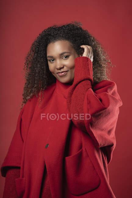 Улыбающаяся женщина с вьющимися волосами в пальто, стоя на красном фоне — стоковое фото