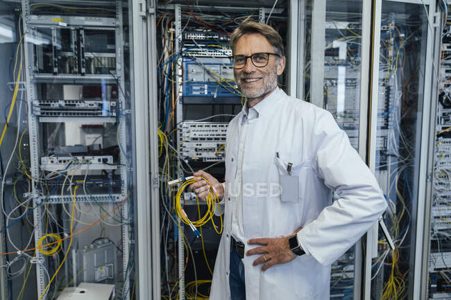 Male IT professional holding cables while standing in data center — Stockfoto