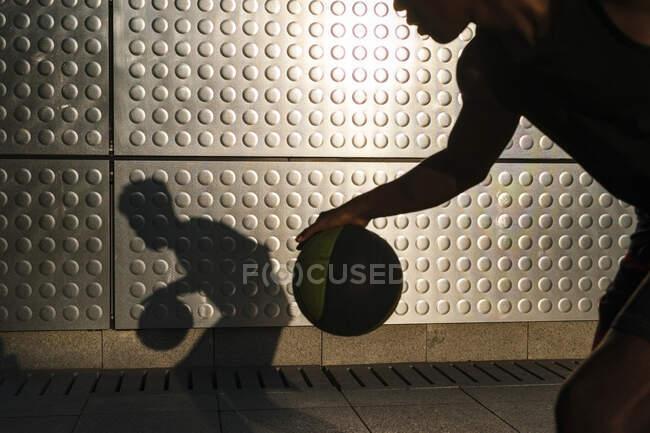 Joven jugando baloncesto en una pared metálica brillante - foto de stock