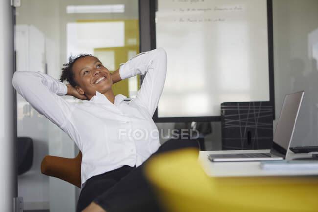 Портрет счастливой деловой женщины, отдыхающей за столом в офисе — стоковое фото