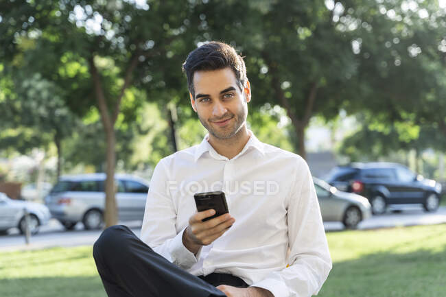 Uomo d'affari fiducioso utilizzando smart phone mentre seduto contro gli alberi — Foto stock