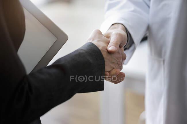 Зв'язок між чоловіками і жінками дає рукостискання в офісі — стокове фото