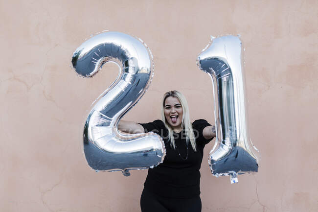 Allegro giovane donna che tiene il numero 21 palloncini mentre in piedi contro il muro — Foto stock