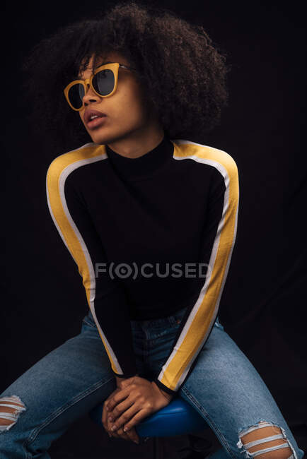 Young woman wearing sunglasses while sitting against black background — Stock Photo