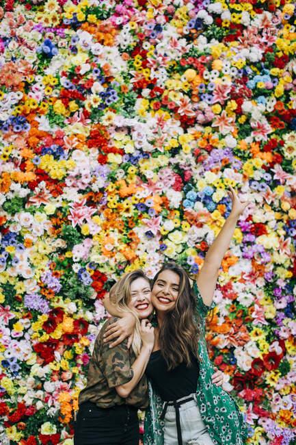 Allegro amici femminili abbracciando mentre in piedi contro fiori colorati — Foto stock