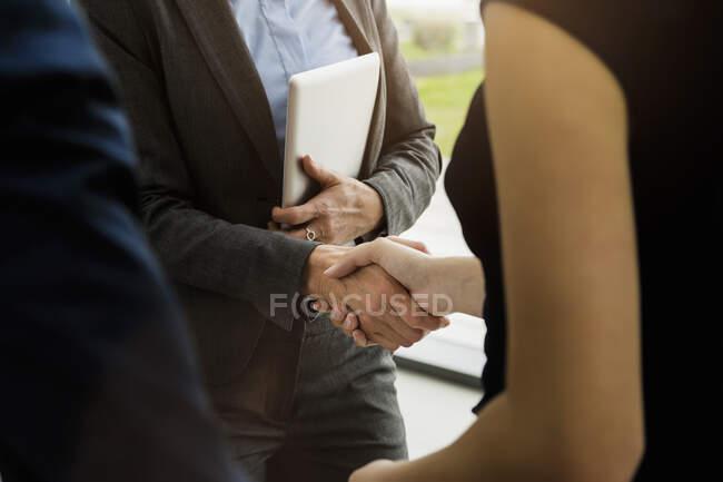 Зблизька ділові люди, які роблять рукостискання в офісі — стокове фото