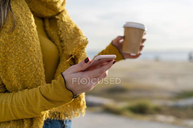 Giovane donna con telefono cellulare e tazza di caffè in piedi all'aperto — Foto stock