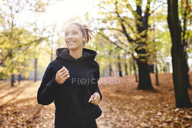 Молодая женщина бегает в осеннем лесу — стоковое фото