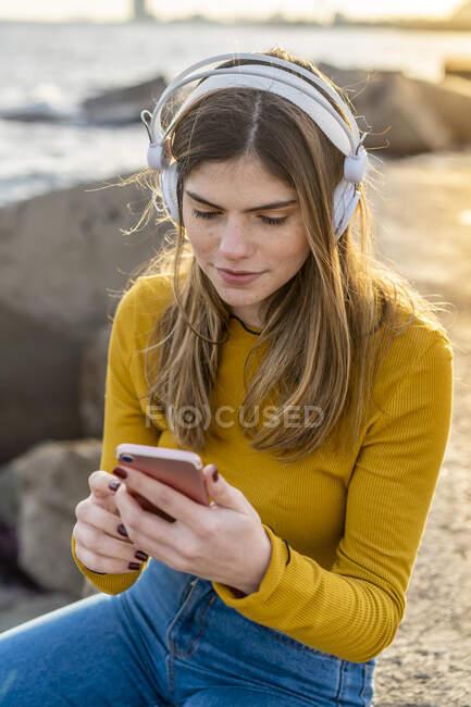 Mujer pensativa con teléfono móvil escuchando música en la ciudad - foto de stock