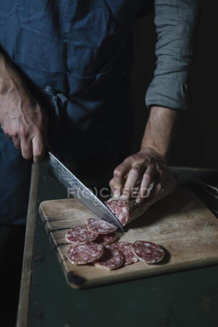 Sección media del hombre cortando rebanadas de salami a bordo en la mesa - foto de stock