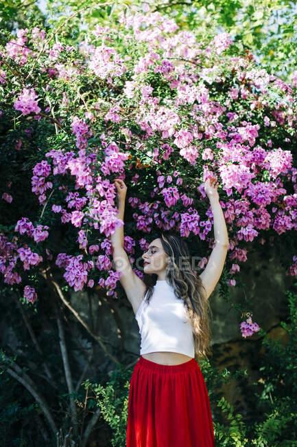 Giovane donna con le braccia alzate in piedi contro le piante nel parco — Foto stock