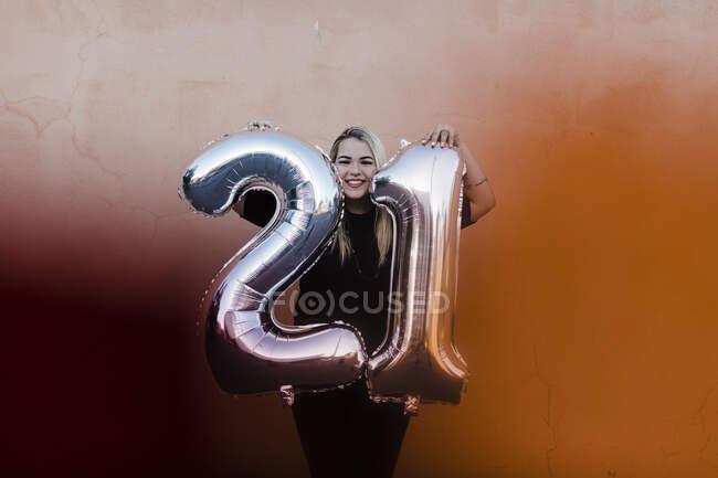 Mujer joven feliz sosteniendo el número 21 globos mientras está de pie contra la pared - foto de stock