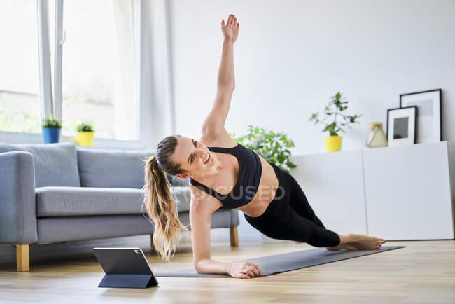 Женщина делает боковую доску упражнения в гостиной на дому — стоковое фото