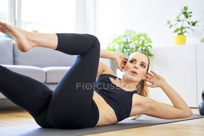 Determined woman exercising in living room at home — Stock Photo