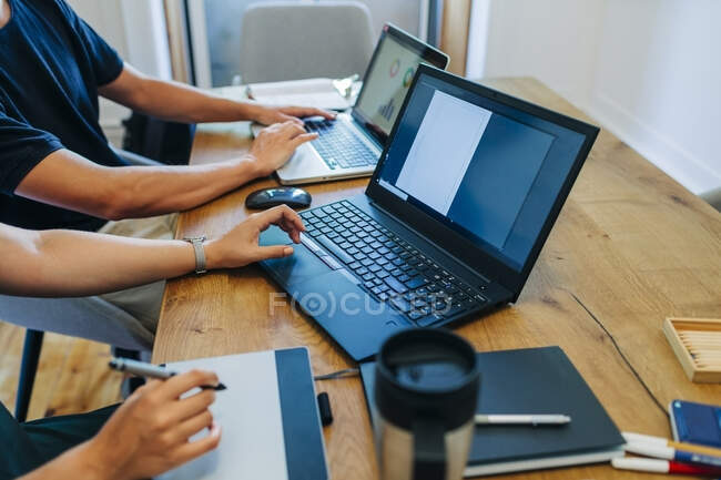 Web designers working while using laptop at office desk — Stock Photo