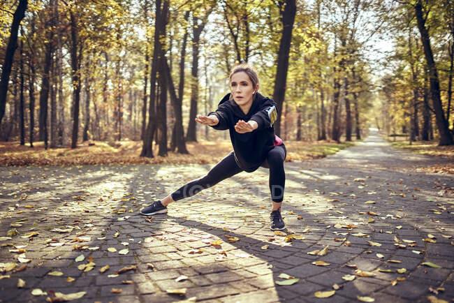 Молодая бегунья растягивает ногу в осеннем лесу — стоковое фото