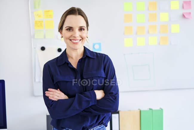 Selbstbewusste Geschäftsfrau steht mit verschränkten Armen im Kreativbüro — Stockfoto