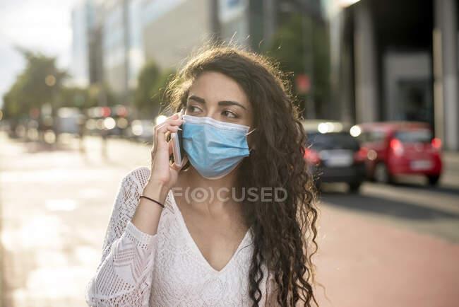Зблизька молода жінка у масці розмовляє по мобільному телефону на вулиці в місті — стокове фото