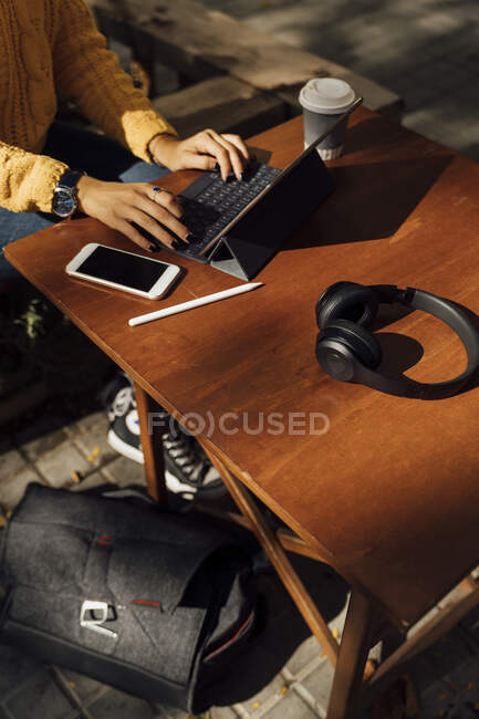Mujer joven usando tableta digital en la mesa del café de la acera en la ciudad - foto de stock