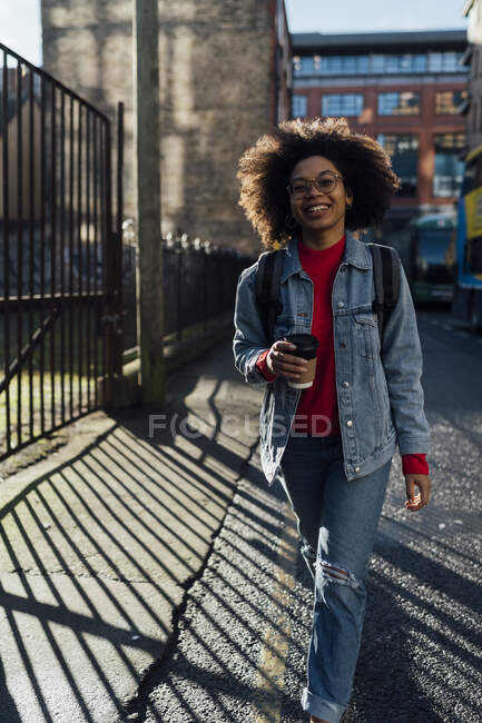 Afro young woman with coffee cup walking on street in city — Stock Photo