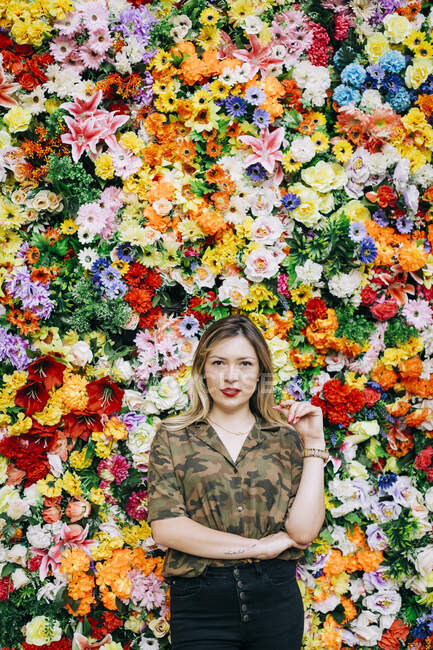Confident beautiful woman standing against colorful flowers — Stock Photo