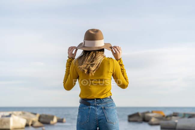 Junge Frau trägt Sonnenhut, während sie am Meer steht — Stockfoto