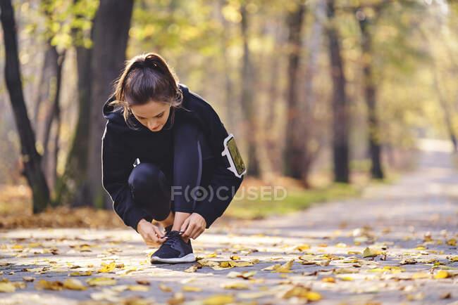Mujer joven atando su zapato de correr - foto de stock