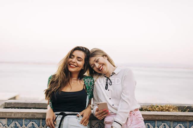 Des amies souriantes les yeux fermés face à la mer — Photo de stock