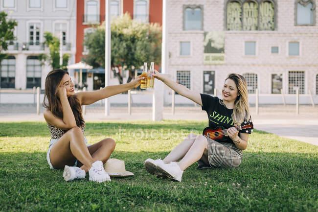 Alegres amigas brindando bebidas mientras están sentadas en tierra herbosa - foto de stock